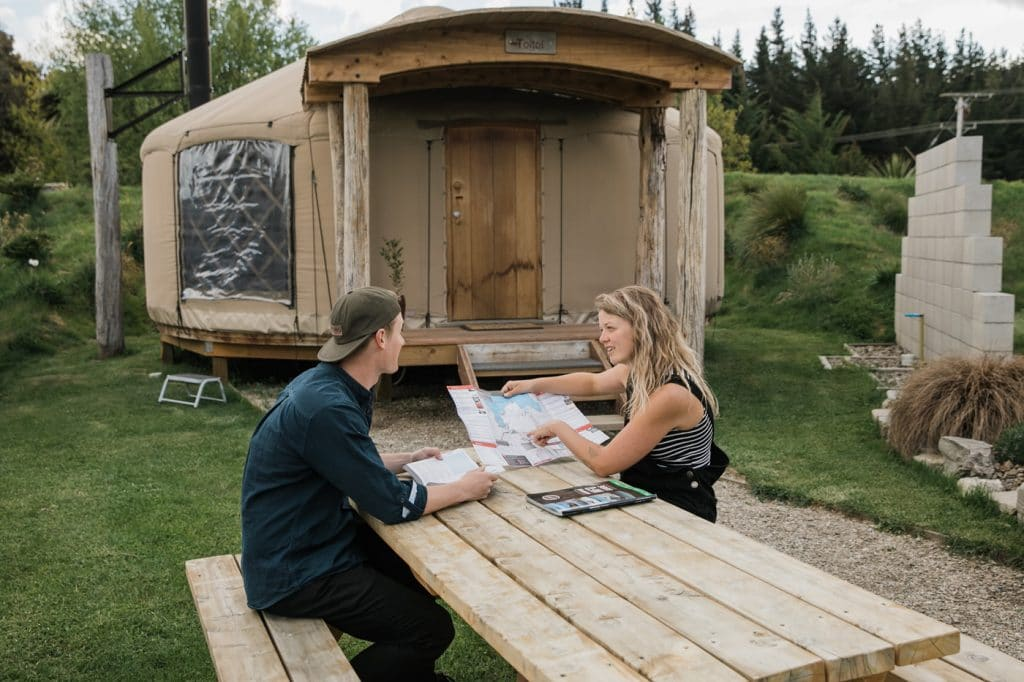 Couple reading map on picnic table outside yurts at Oasis Yurt Lodge Wanaka