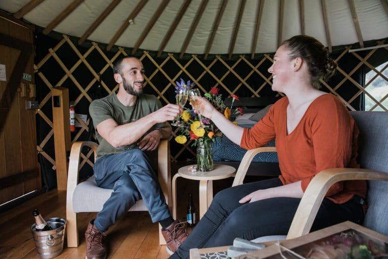 Couple enjoying drinks & special occasion package at Oasis Yurt Lodge, Wanaka