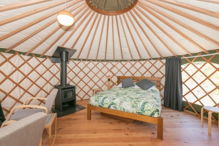 Interior of Queen Yurt with queen bed & fireplace at Oasis Yurt Lodge Wanaka