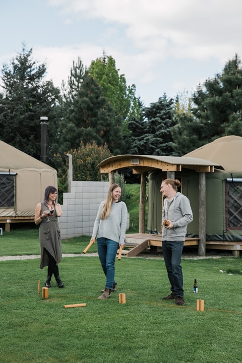 Group playing game of Kubb on lawn by yurts at Oasis Yurt Lodge, Wanaka New Zealand