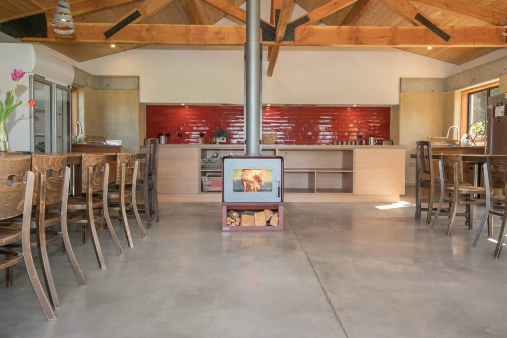 Shared kitchen & dining facilities with fireplace at Oasis Yurt Lodge Wanaka